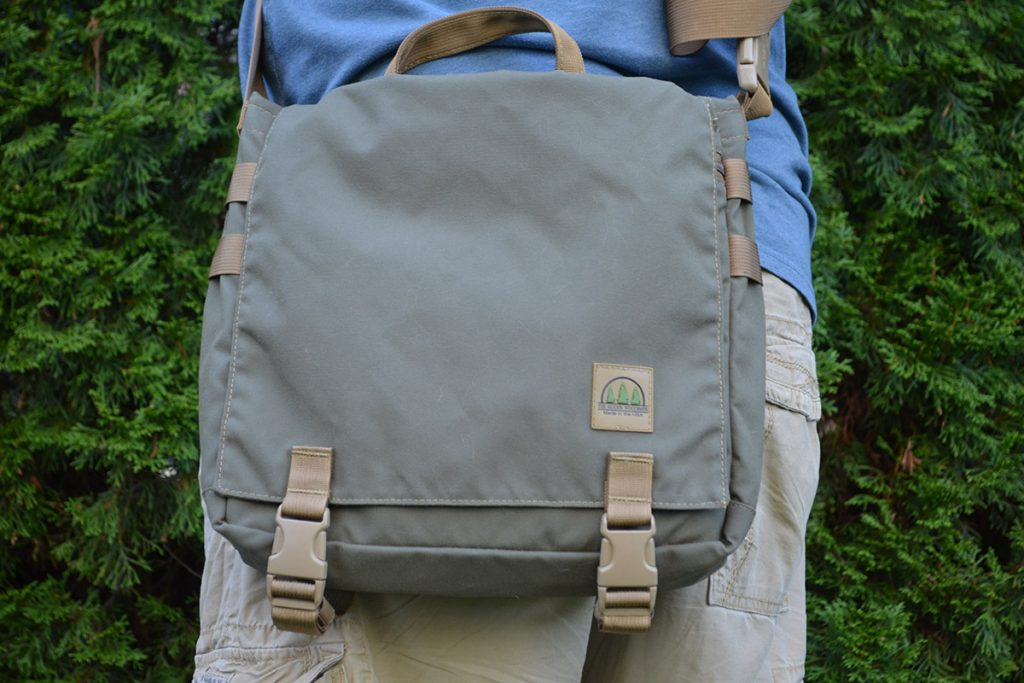 I often carry the bag so it hangs over my backside, so as to not interfere with my arms as I walk.